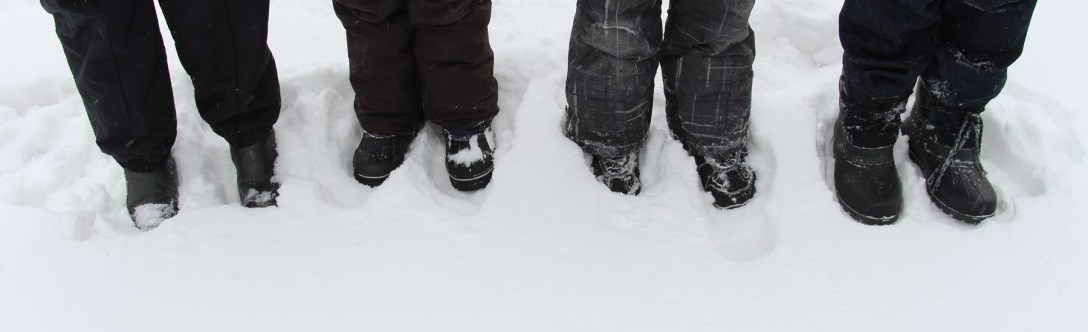 Image of 4 people's feet in the snow