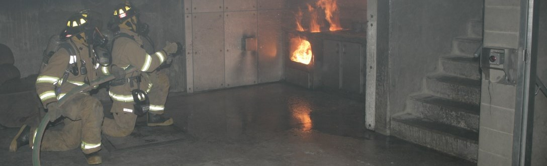 Two fire fighters in a training centre practicing putting out an oven fire