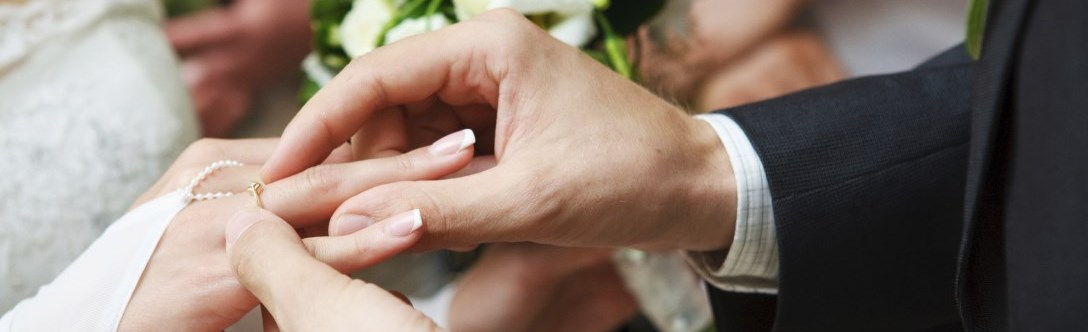 Hand putting wedding ring on another person's hand