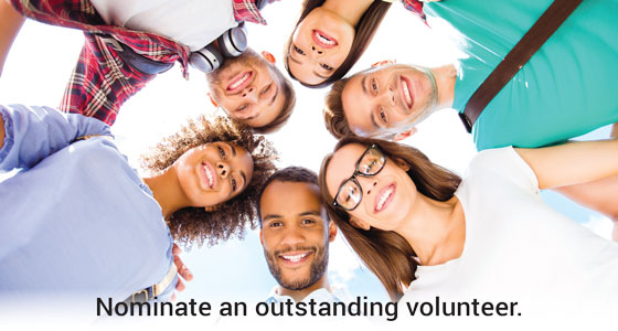 Group of people huddled up with text below saying 'Nominate an outstanding volunteer'