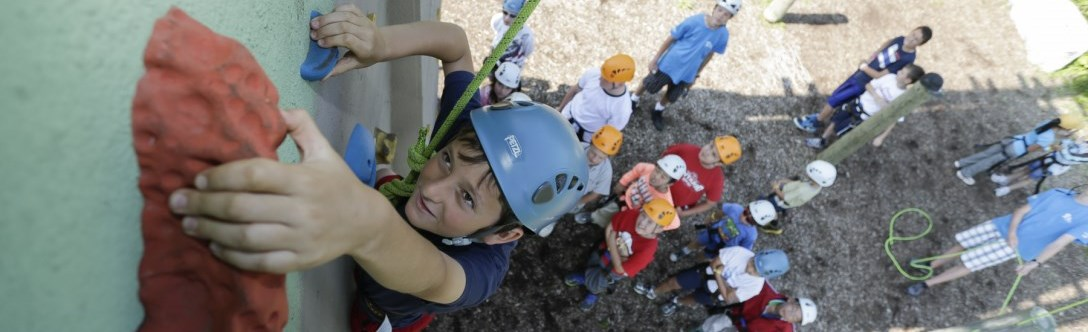 Child on climbing wall and other children waiting below for their turn
