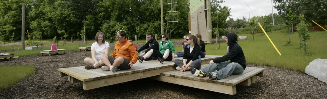 Group of people balancing out on a platform together at eyer homestead ropes course in Richmond Hill
