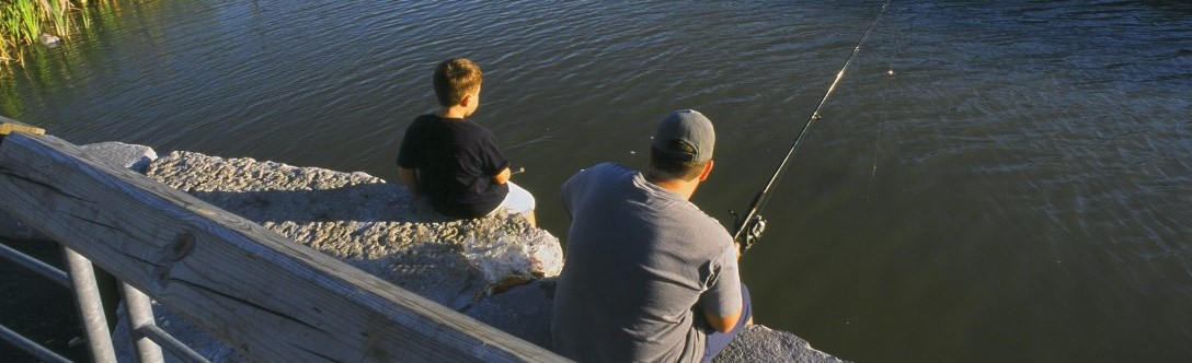 Father and son sitting on a rock and fishing at Headwaters Park