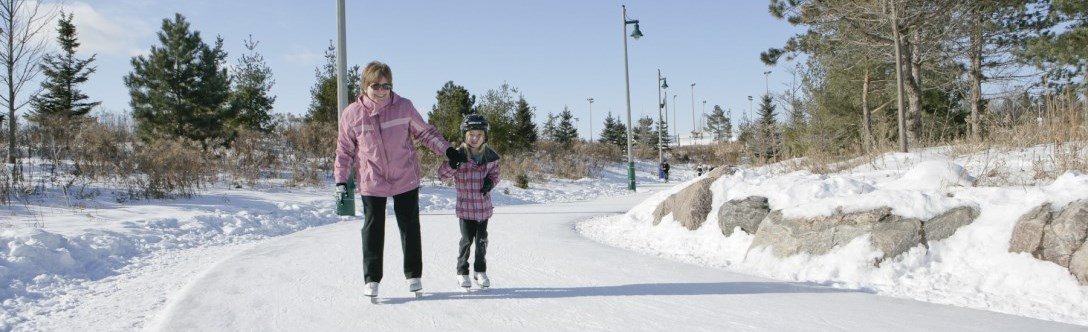 A mom and daughter skating on the outside trail at Richmond Green