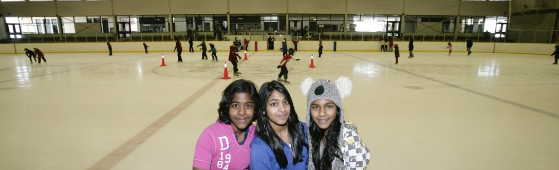 Three young girls posing for a photo while at a public skate with many people skating behind them