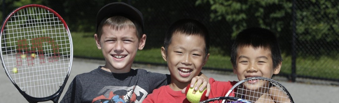 Three young boys outside playing tennis and smiling
