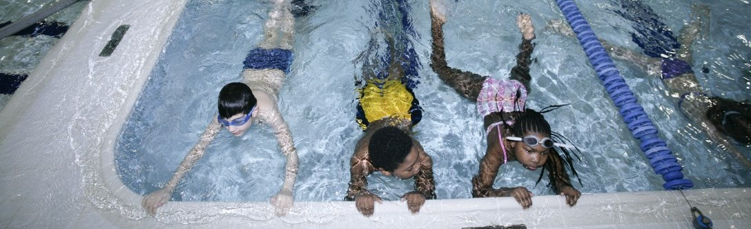 Kids holding onto edge of pool during swim lessons