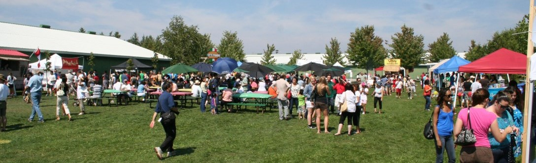 Open field with tables full of people eating in the food village tastes of the hill in Richmond Hill